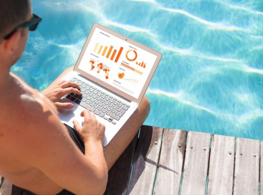 Businessman working on laptop computer by the pool