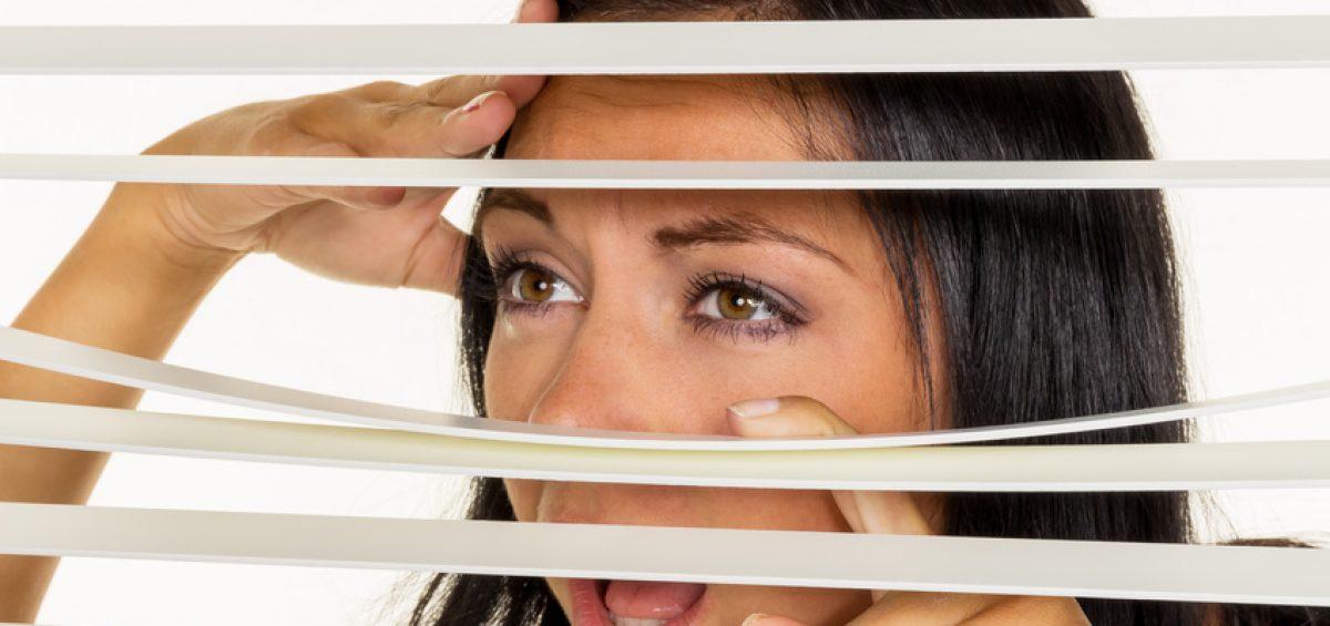 Eine junge Frau beobachtet etwas durch die Jalousie ihres Fensters
