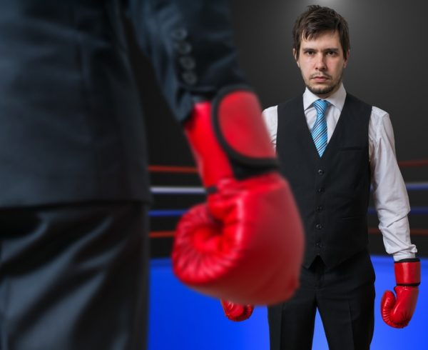 Businessman is boxing with his boss in ring.