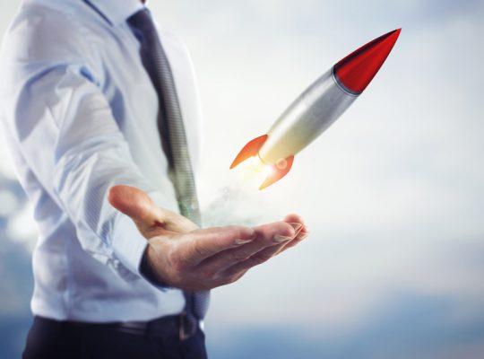Businessman holding a small rocket. Startup working enterprise concept