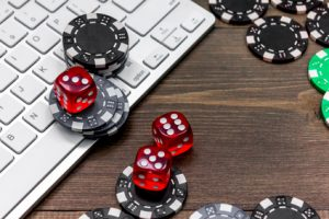 Online poker. Chips and the dice nearby keyboard on wooden table top view.