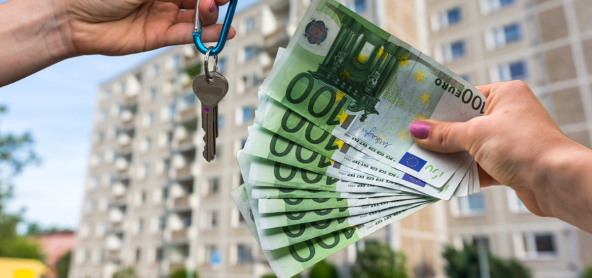 Real estate agent giving apartment keys to a new property owner, who is paying by euro money on blurred background