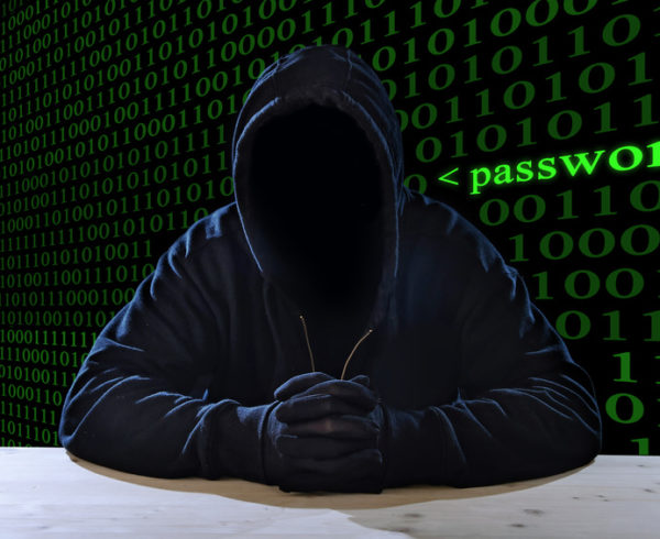 criminal or terrorist man in gloves, black hood and thief mask looking dangerous with hidden identity in secret illegal password violation and crime concept with creepy scary terrorist and maniac look