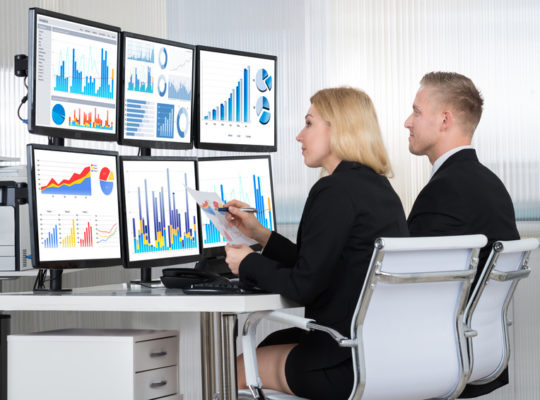 Young financial analysts using computers at desk in office